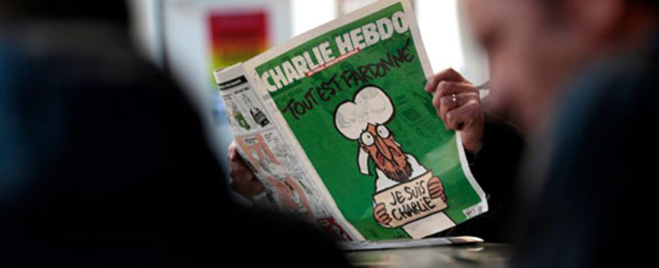 A man poses with the new issue of French satirical weekly Charlie Hebdo at a cafe in Nice